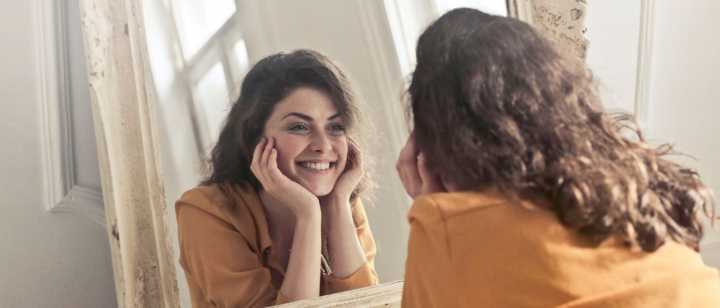 girl smiling in front of mirror